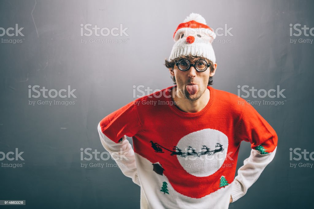 Moody man in funny christmas clothes sticking out his tongue stock photo