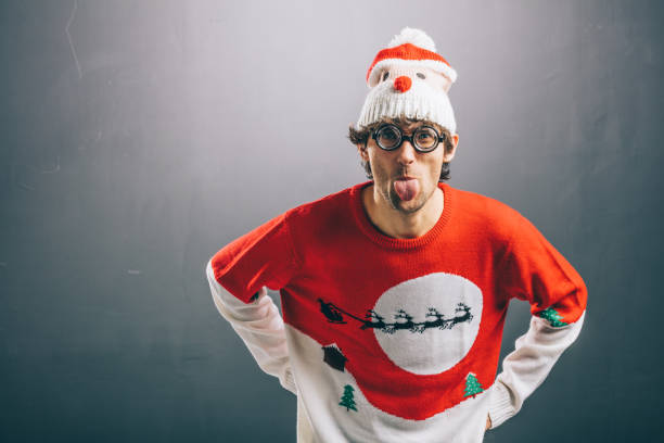 Moody man in funny christmas clothes sticking out his tongue Moody man sticking his tongue out, dressed in funny glasses, christmas sweater and beanie. Christmas concept. ugliness stock pictures, royalty-free photos & images