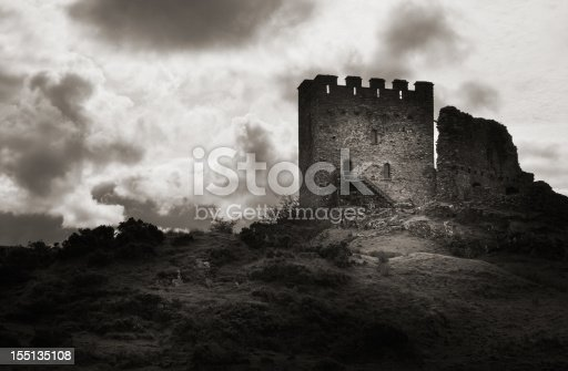 Moody Black and white photo with a vintage look and eerie lighting, featuring a dark Dolwyddelan Castle with a rogue ray of sun illuminating the main building.