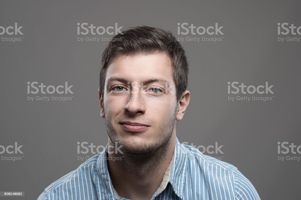 Moody portrait of young man in shirt with smirk smile stock photo