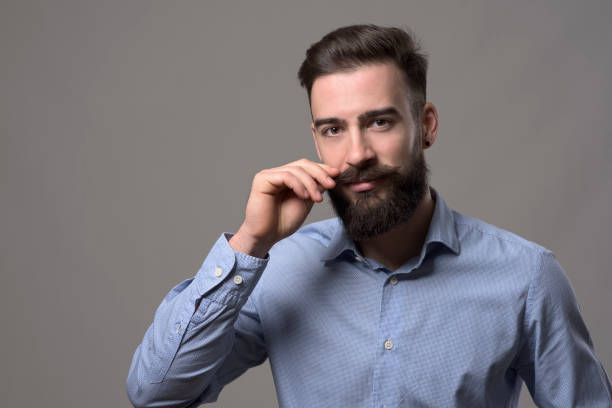 Moody portrait of young stylish bearded man twirling mustache and looking at camera Moody portrait of young stylish bearded man twirling mustache and looking at camera over gray studio background with copyspace. mustache stock pictures, royalty-free photos & images