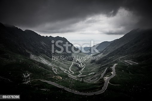 A dark and ominous sky hangs over the rugged Carpathian mountains and the Transfagarasan road that winds through this dramatic landscape in Transylvania, Romania. The Transfăgărășan or DN7C, also known as Ceaușescu's Folly, is a paved mountain road crossing the southern section of the Carpathian Mountains of Romania. It has national-road ranking and is the second-highest paved road in the country after the Transalpina.