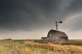 A moody sky over an abandoned barn and windmill in a stubble field on the prairies in Saskatchewan, Canada