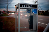 Empty telephone booth along a highway.