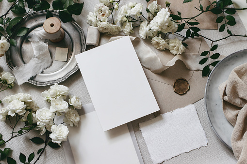 Moody wedding table mockup scene. Feminine desktop composition with fading white rose flowers, silver plate, silk ribbons, seal stamp, envelopes and blank greeting cards. Grey background. flat lay,top