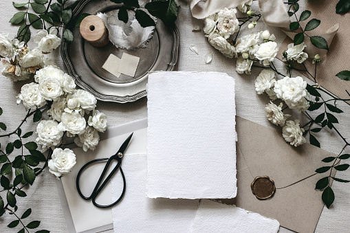 Moody wedding table mockup scene. Stationery composition with fading white rose flowers, silver plate, black scissors, envelopes and blank greeting cards. Grey textured background, flat lay, top view.