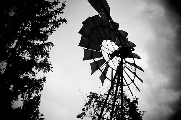 Moody windmill image against a cloudy sky. stock photo