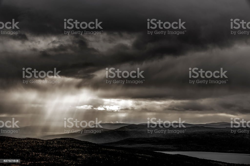 Moody woodland and lake landscape with sun beams comming through rain...