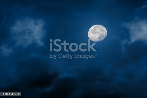 Moon at night with bright and dark clouds on blue background, concept of horror and Halloween