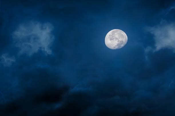 moon at night with bright and dark clouds on blue background - céu a noite imagens e fotografias de stock