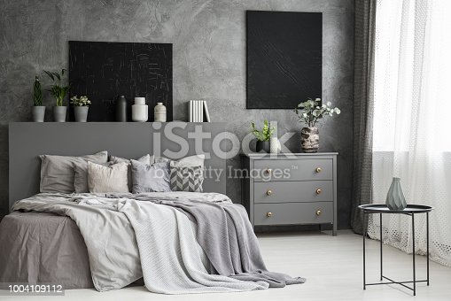 508860888 istock photo Moon canvas on a grey wall in a monochromatic cozy bedroom interior with a bed with cushions, bedding an a blanket. Real photo 1004109112