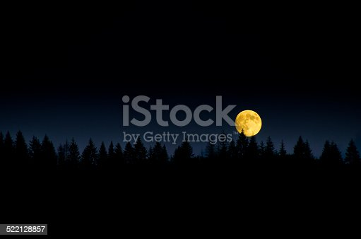 478539432 istock photo Moon close up with trees over the mountain. 522128857