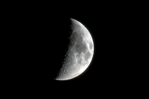 Close-up of half moon with visible impact craters.