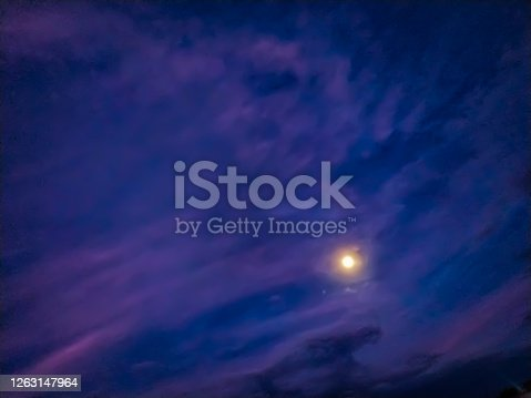 A moon glowing in running fluffy clouds in sky at night
