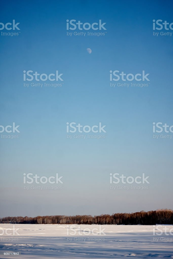 moon in day sky on winter landscape stock photo