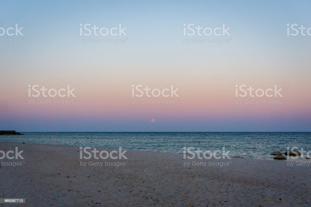 Moon is rising over idyllic Bornholm, Denmark on a day in summer stock photo