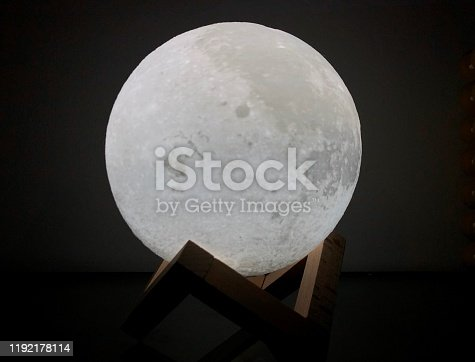 Moon lamp bright night light with astonishing design laying on top of a symmetric shape.