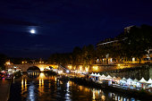 Rome, Italy - August 20, 2013: Roman dwellers and tourists spend leisurely time at the river banks of Fiume Tevere under the rising moon at night