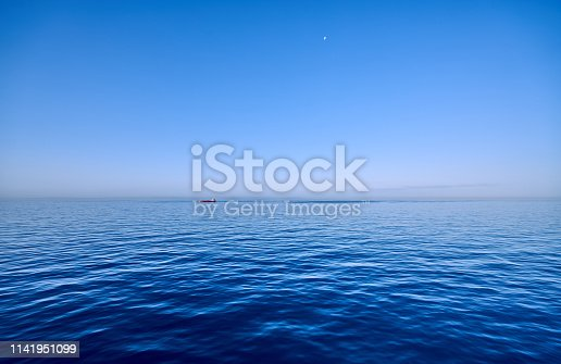 Panoramic view at blue-shimmering north sea in the morning time. While the moon is still visible in the sky, a red ship passes the sea on the horizon.