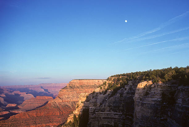 Moon over the Grand Canyon The moon flies over cliffs of the Grand Canyon with ample room in the sky for copy space hearkencreative stock pictures, royalty-free photos & images