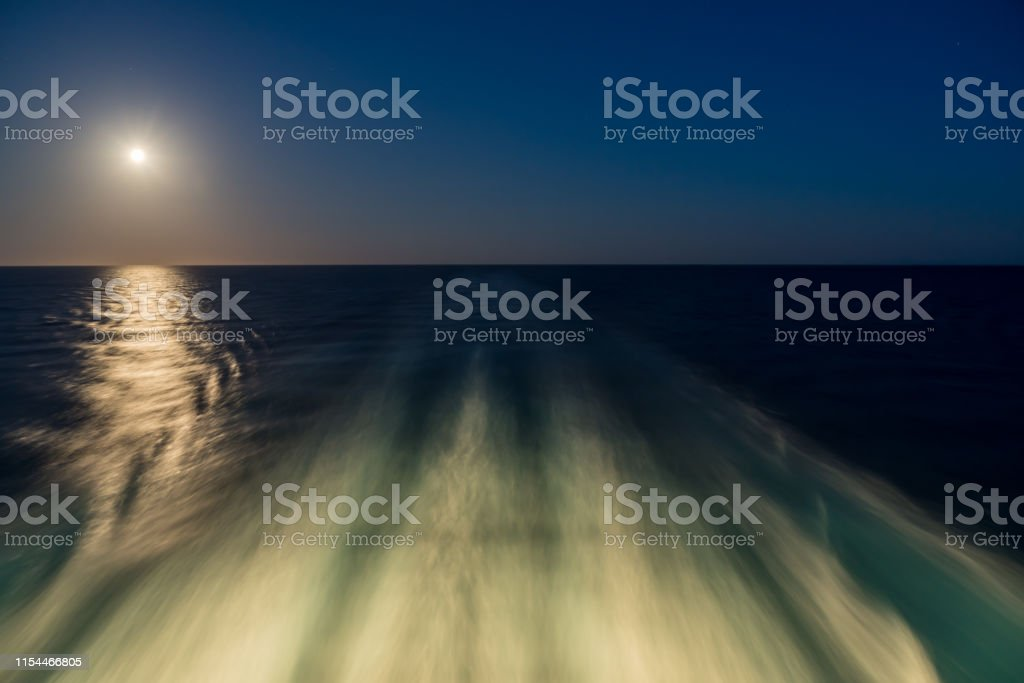 Moon rising over wake and waves of cruise ship at sea with concept of...