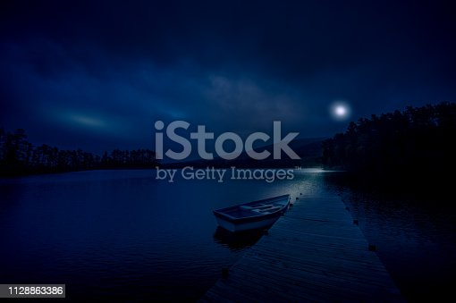 Night scene of a Moored rowboat on a lake next to a wooden jetty overlooking mountains and woodlands with the moon behind the clouds reflecting on the water in the Cape Winelands South Africa