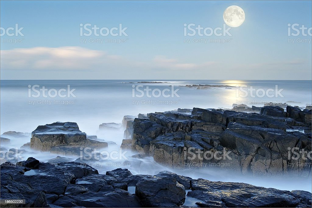 Moon rises smooth pale blue sea Snook Point Newton Northumberlan royalty-free stock photo