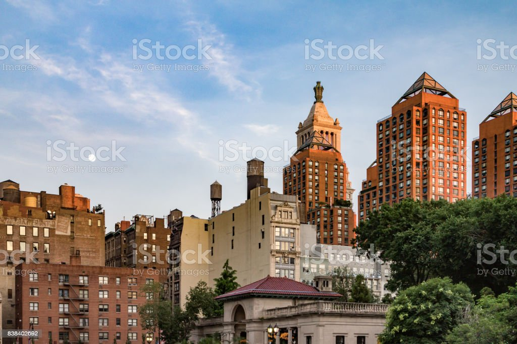 Moon rising in the sky above Union Square Park at dusk in Manhattan, New York City NYC stock photo