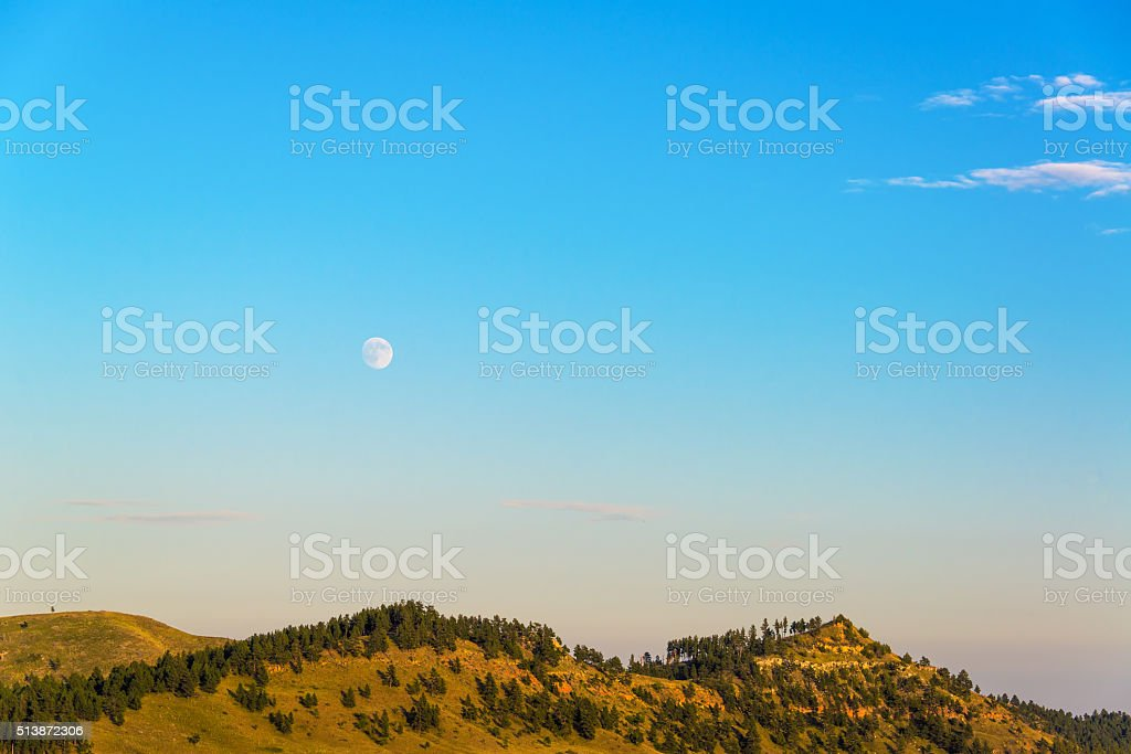 Moon Rising over Hills stock photo