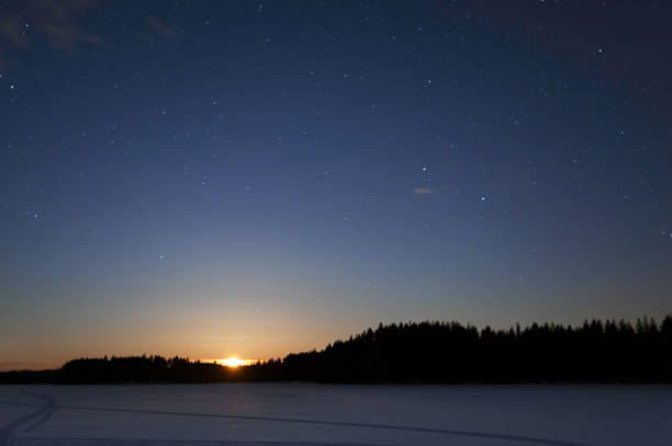 Moon rising over winter landscape at night stock photo