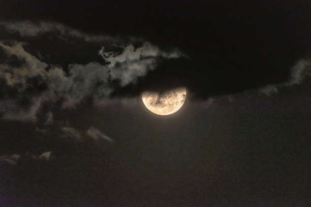 Moon rising through the clouds stock photo
