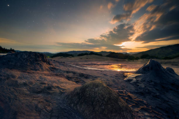 Moon set scene in the night with a starry sky at the muddy volcanoes, Vulcanii Noroiosi in Romania Buzau County stock photo