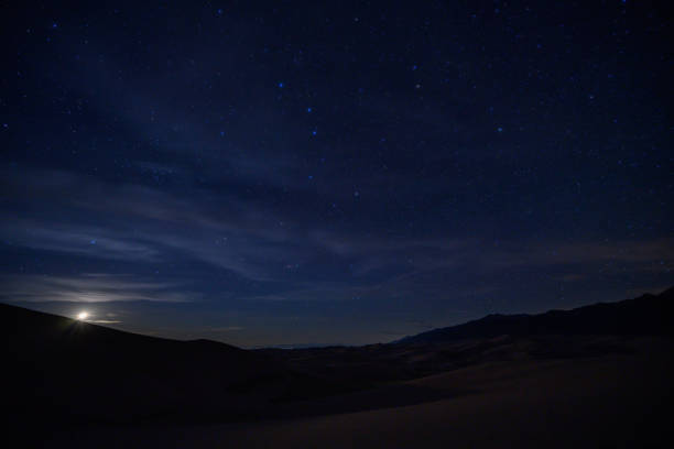 Moon Sets Below Sand Dunes and Star Field stock photo