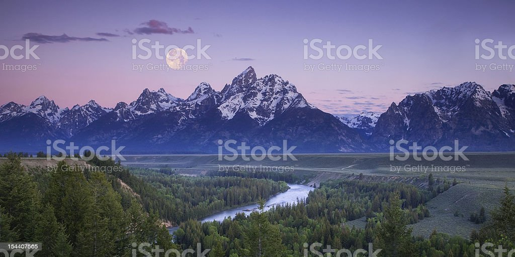Moon setting over the Tetons stock photo