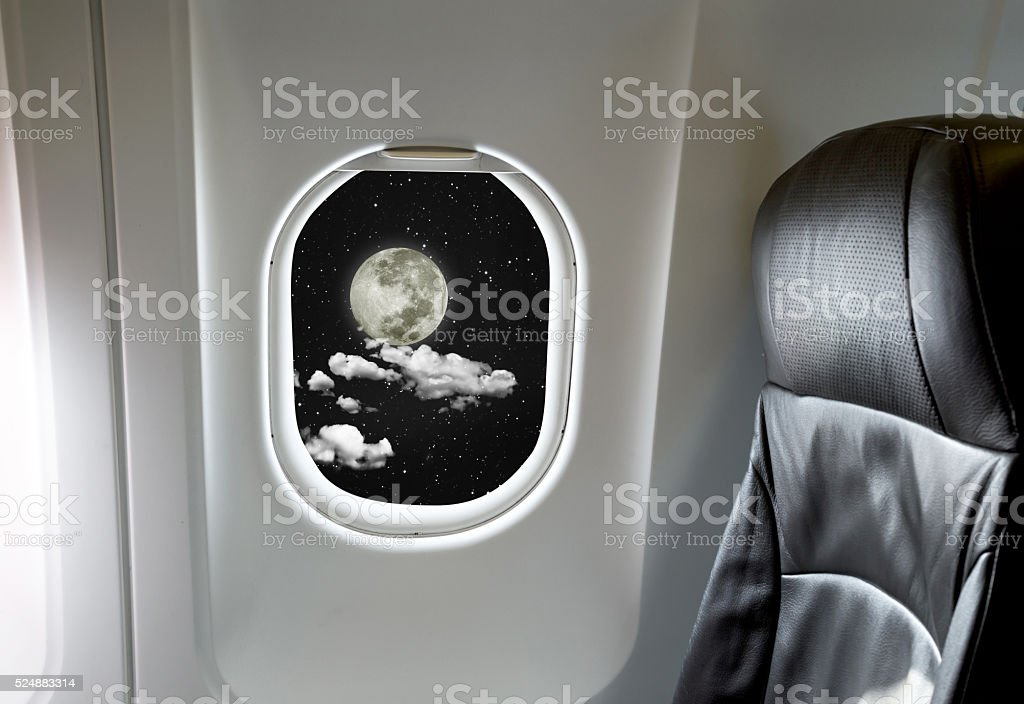Moon through aircraft window onto jet engine stock photo