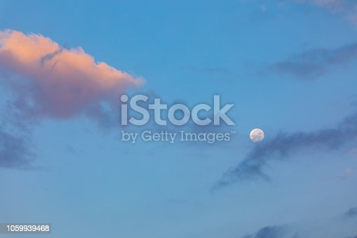 Moon with sun lightened cloud at morning sky
