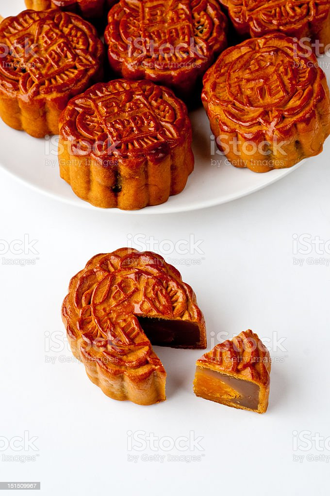 Mooncake with a section removed A Chinese moon cake with a section removed. Several moon cakes in the background. Cake Stock Photo
