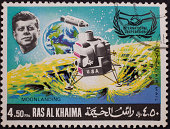 'Moonlanding commemorative stamp from the emirate of Ras Al Khaima, featuring John F. Kennedy and the Lunar Module.'