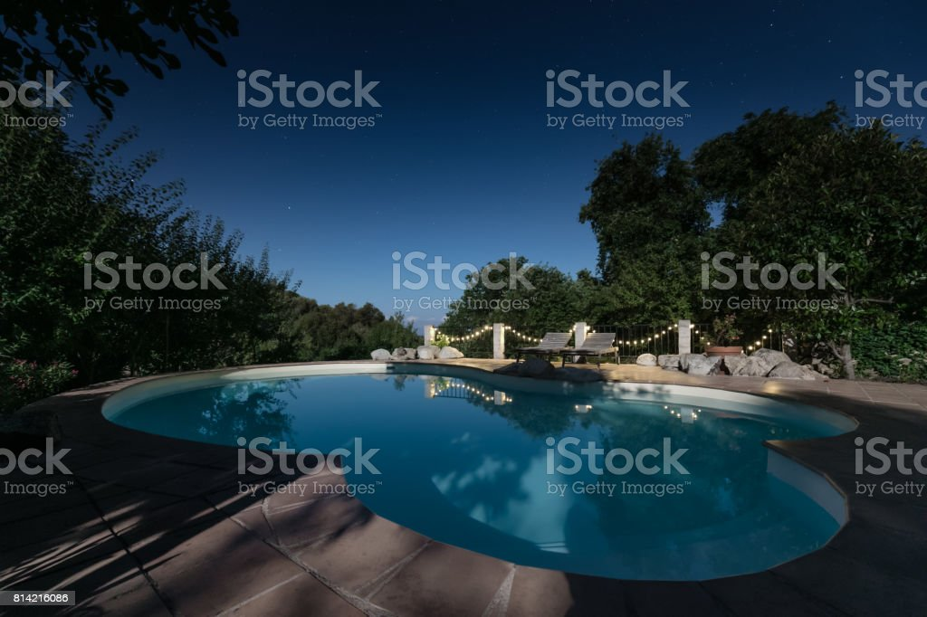 Moonlight and night sky reflected on a swimming pool stock photo