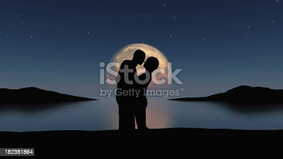 Couple embracing in front of an over sized moon reflected in calm water.