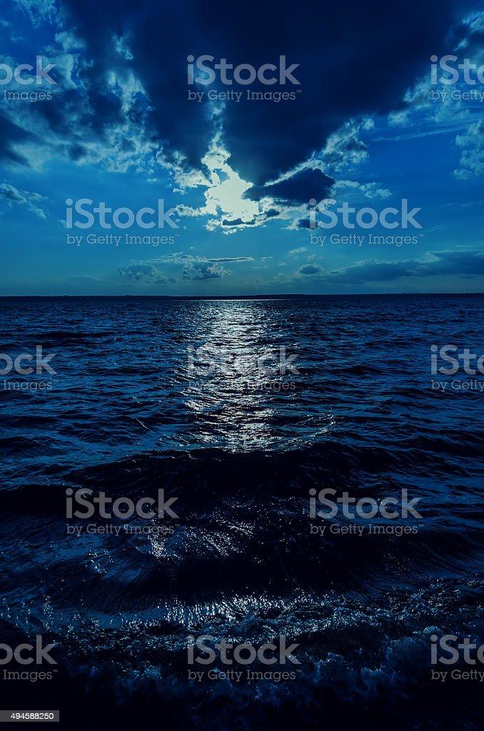 moonlight in sky over dark water stock photo