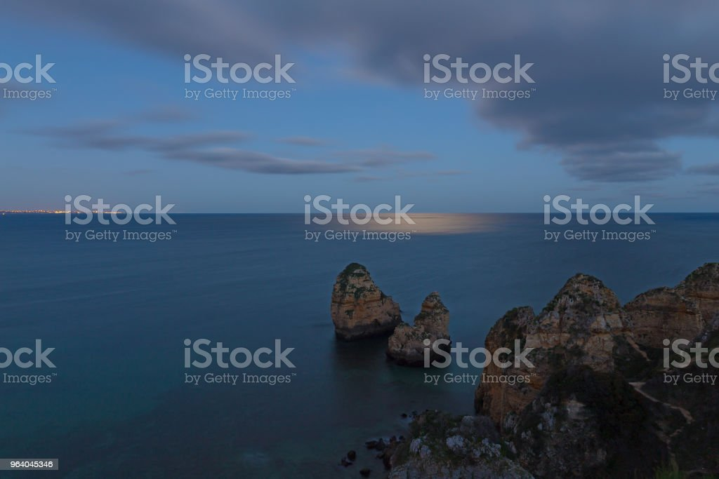 Moonlight on a sea surface and distant town on over the water horizon. - Royalty-free Algarve Stock Photo