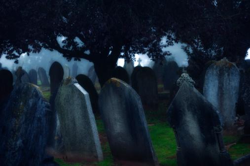 Moonlight Shines Over Dark Misty Cemetery Tombstones