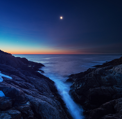 The Waning Crescent Moon above a narrow cove washed in the Atlantic.  Long exposure in pre-dawn light.