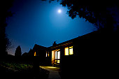 A wooden house lit by the moon.