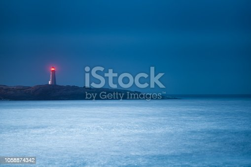 A long exposure of a moonlit lighthouse on a slightly foggy night.
