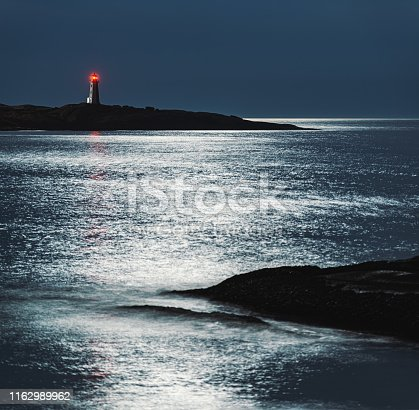 Light of the Full Moon falling on iconic Peggy's Cove Lighthouse.