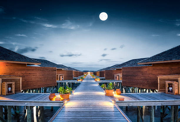Moonwalk overwater bungalows boardwalk on maldives at full moon night  beach hut stock pictures, royalty-free photos & images