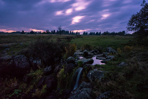moor landscape with creek and waterfall under cloudy sky dark in twilight atmosphere at Roehn Mountains, Germany