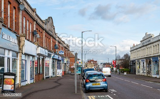 Bournemouth, UK. 5th February 2020: Shops line the high street of Moordown, a suburb of the town of Bournemouth, UK. Cars parked on the road.